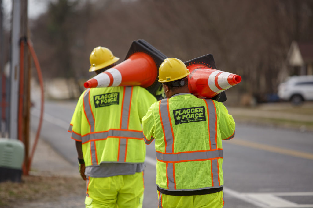 Employees working together carrying cones while setting up a work zone
