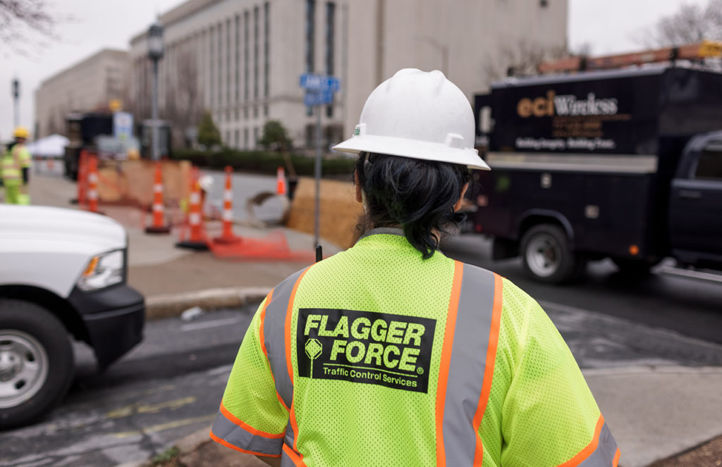 Back of Flagger Force employee in PPE on job site with eciWireless truck