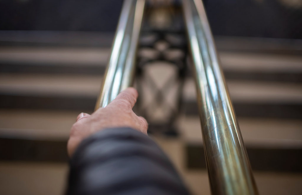 Hand on metal stair railing