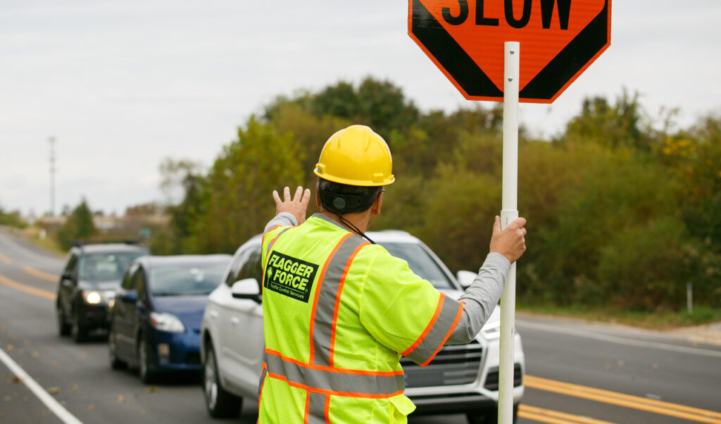 Flagger Force employee stops vehicle in work zone